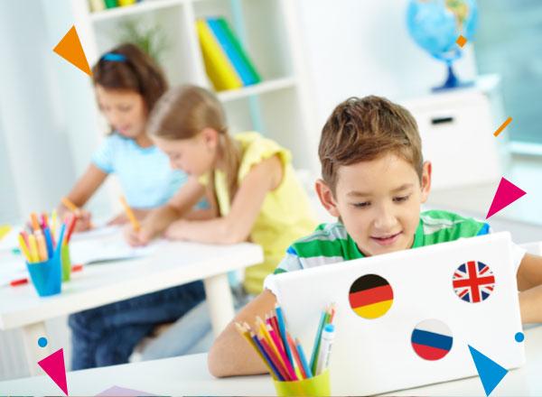 Chłopiec uczy się przy laptopie z naklejonymi flagami państw