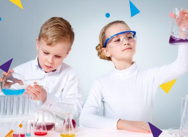 Dzieci ubrane na biało wykonują eksperymenty chemiczne