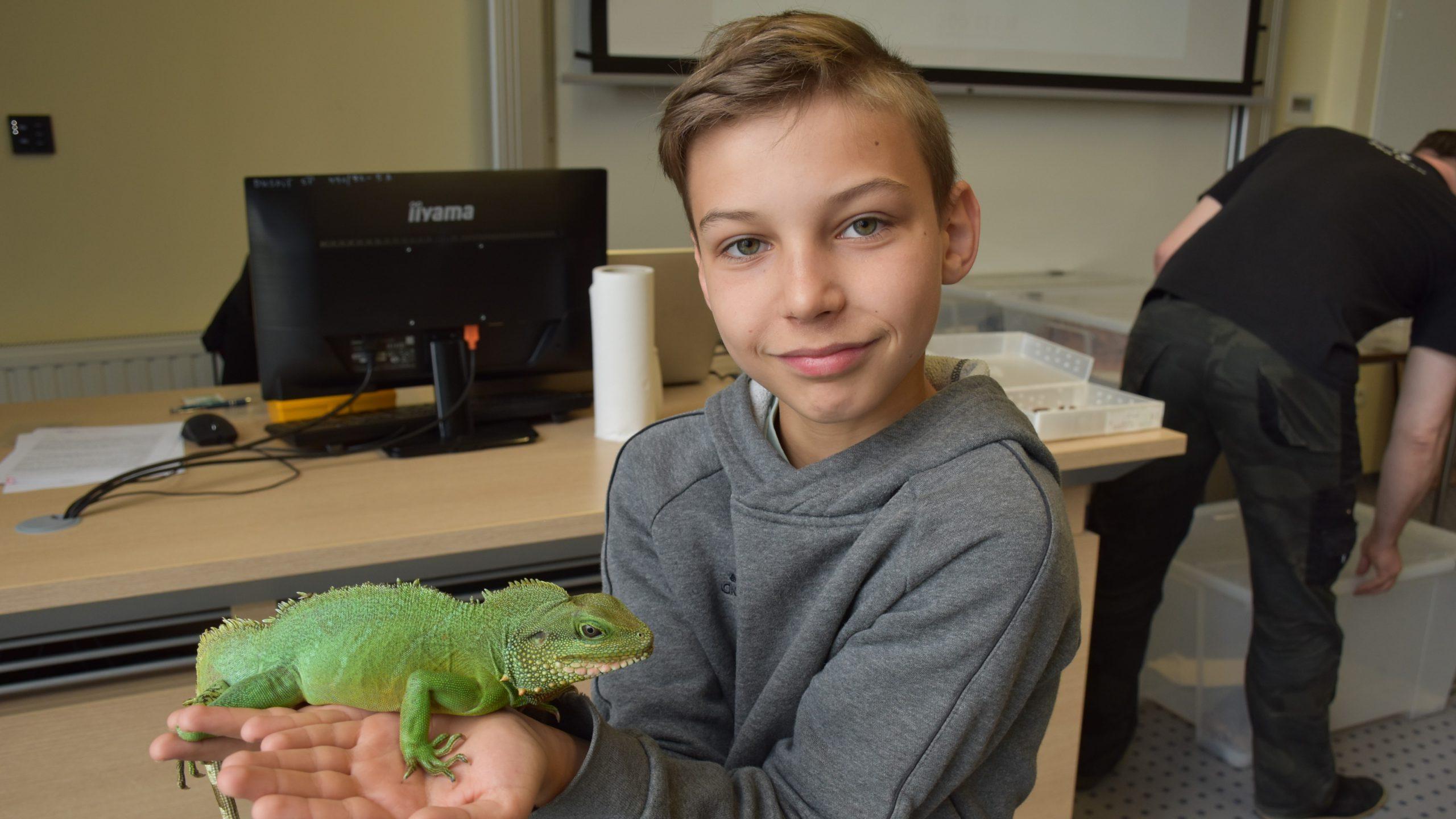 chłopiec trzymający na rękach kameleona